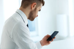 Leitura do homem de negócio algo na tela de seu telefone celular Fotos de Stock