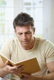 Leitura do homem em casa Foto de Stock Royalty Free