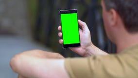 Leitura do homem em um telefone celular handheld filme