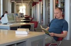 Leitura do homem na biblioteca   Imagem de Stock