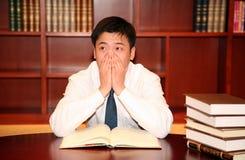 Leitura do homem na biblioteca Fotos de Stock Royalty Free