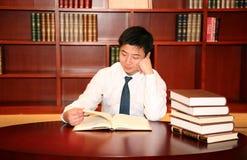 Leitura do homem na biblioteca foto de stock royalty free