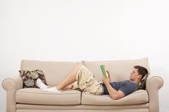 Leitura do homem no sofá Fotos de Stock