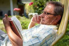Leitura do homem sênior ao ar livre Foto de Stock Royalty Free