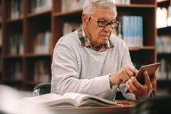 Leitura do homem sênior em uma biblioteca imagens de stock