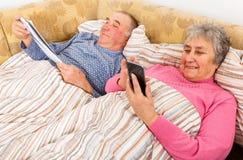 Leitura do homem superior e sua esposa que surfam o Internet imagens de stock royalty free
