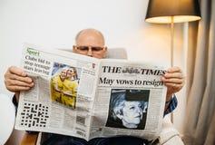 Leitura do homem superior na imprensa do Reino Unido do Times da sala de visitas sobre Brexit fotografia de stock