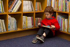 Leitura do menino em uma biblioteca Fotografia de Stock Royalty Free