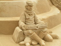 Leitura do menino na areia fotografia de stock royalty free