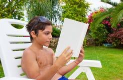 Leitura do menino no gramado do verão fotografia de stock royalty free