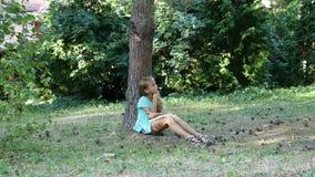 Leitura do verão sob a árvore Um adolescente lê um livro exterior filme