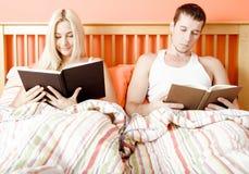 Leitura dos pares na cama fotos de stock