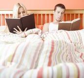 Leitura dos pares na cama fotografia de stock