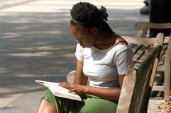 Leitura em um banco de parque Imagens de Stock