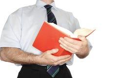 Leitura em um livro vermelho Fotos de Stock