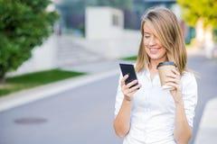 Leitura esperta nova da mulher profissional usando o telefone Fotografia de Stock
