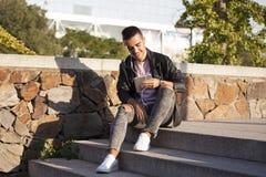 Leitura feliz do homem novo em uma tabuleta ou escuta a música no fotografia de stock royalty free