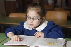 Leitura italiana do primeiro-graduador da menina da escola primária na escola Imagens de Stock