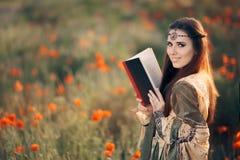 Leitura medieval um livro em um campo mágico das papoilas imagem de stock