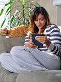 Leitura multiracial bonita da mulher com gato imagens de stock
