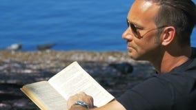 Leitura no lazer - um homem relaxa no fim de semana no parque da cidade video estoque