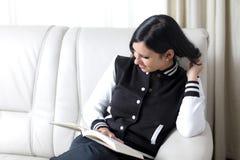 Leitura no sofá Fotos de Stock
