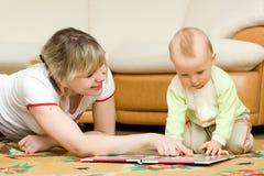 Leitura nova da mamã seu livro pequeno do filho em um assoalho foto de stock royalty free