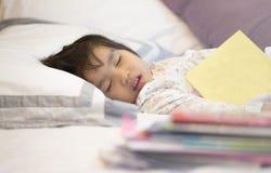 Leitura pesada dos deveres do sono cansado da menina fotos de stock