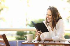Leitura relaxado da mulher um livro em um ebook Fotografia de Stock Royalty Free