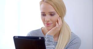 Leitura séria da jovem mulher em sua tabuleta video estoque