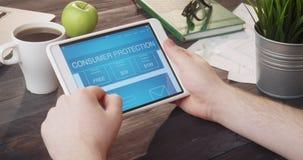 Leitura sobre a proteção ao consumidor usando o tablet pc na mesa vídeos de arquivo