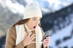 Leitura surpreendida da mulher na linha notícia no inverno foto de stock