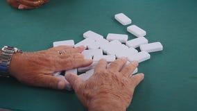 Lek av dominobricka` s som spelas av män arkivfilmer