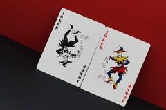 Lek av fantasi Kortallegorin är röd och svart som symbol av motsatser och motsättningar i värld Röd och svart joker på royaltyfria bilder