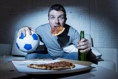 Lek för fotboll för fotbollsfanman hållande ögonen på på den hemmastadda soffan för tv att uttrycka med fotbollbollen och pizza i royaltyfria bilder