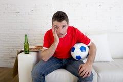 Lek för fotboll för man för ung fan hållande ögonen på på för lagärmlös tröja för television nervöst bärande lidande och spänning Fotografering för Bildbyråer