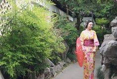 Lek för kimono för traditionell asiatisk japansk kvinnabrudGeisha bärande i en gradenhåll ett rött paraply Royaltyfri Bild