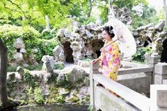 Lek för kimono för traditionell asiatisk japansk kvinnaGeisha bärande i en gradenställning på en brohåll ett vitt paraply Royaltyfria Foton