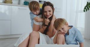 Lek för mamma som och för två barn sitter på golvet som kramar och har gyckel lycklig familj Leken, når att ha beskådat bärbara d arkivfilmer