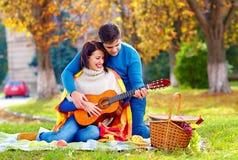 Lek för manundervisningflicka en gitarr på höstpicknick Arkivbild