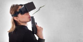 Lek för skytt för kvinnalek VR med virtuell verklighetvapnet och vrexponeringsglas Arkivfoton