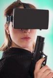 Lek för skytt för kvinnalek VR med virtuell verklighetvapnet och vrexponeringsglas Arkivfoto