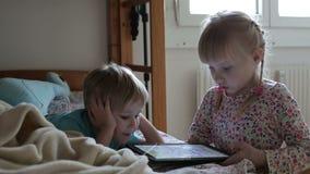 Lek för små barn spelar på minnestavlan i sängen och leendet arkivfilmer