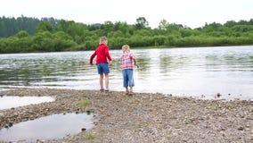 Lek för två barn på flodbanken Kaststenar, gör färgstänk av vatten Härlig sommarliggande lager videofilmer