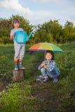 Lek för två bröder i regn utomhus Royaltyfri Foto
