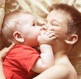 Lek för två bröder i säng för läggdags royaltyfri foto