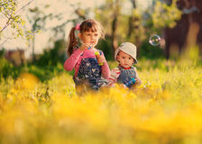 Lek för två flickor med såpbubblor på våren royaltyfria bilder