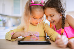 Lek för två lilla systrar på en minnestavlaPC Arkivbilder