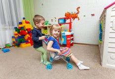 Lek för två lycklig barn med leksaksittvagnen i daycare arkivbild