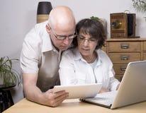 Lek för två pensionärer med en minnestavladator arkivfoto